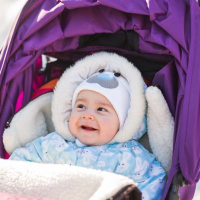 Funny laughing baby sitting in a stroller on c old winter day