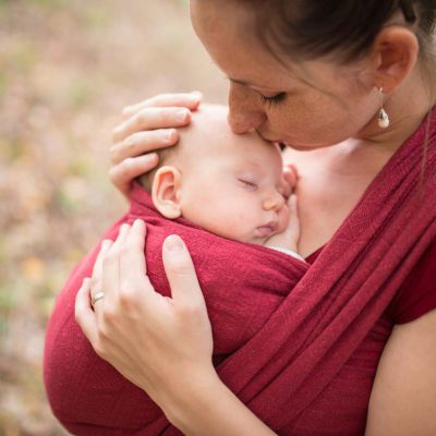 Mother holding her baby daughter, outside in autumn nature