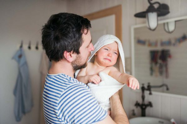 Father with a toddler child wrapped in towel in a bathroom at home.